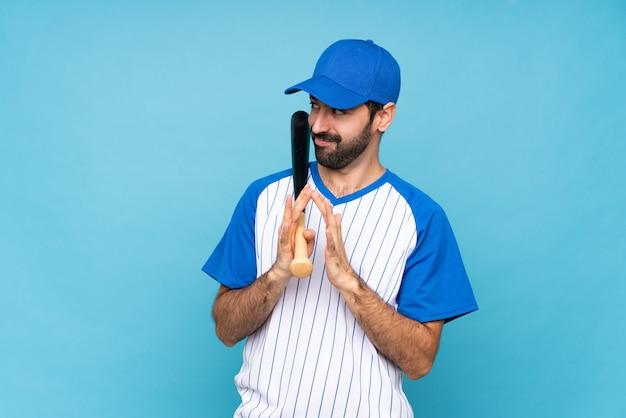 Jovem jogando beisebol sobre azul isolado planejando algo