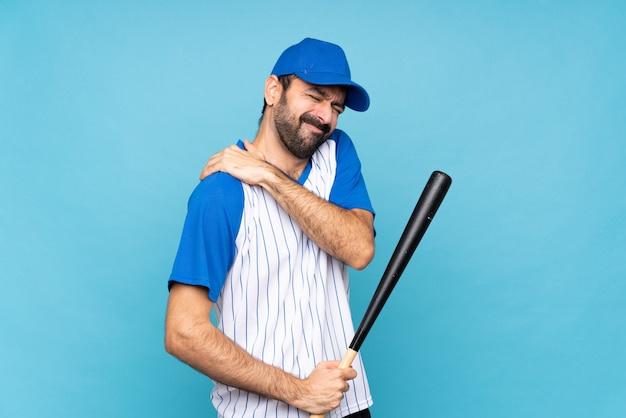 Jovem jogando beisebol sobre azul, sofrendo de dor no ombro por ter feito um esforço
