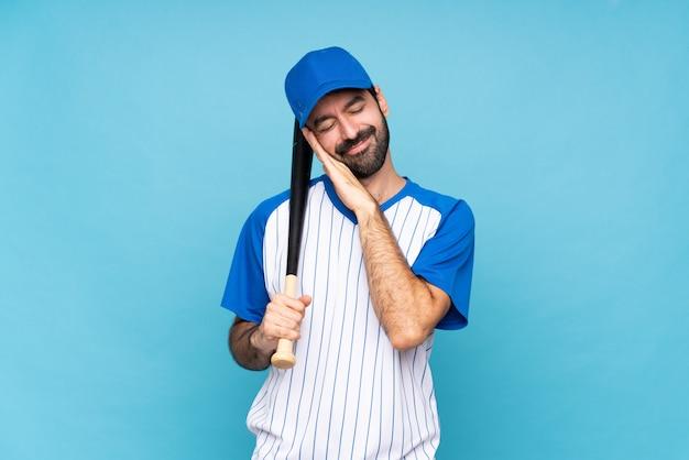 Jovem jogando beisebol sobre fundo azul isolado, fazendo o gesto do sono na expressão dorable