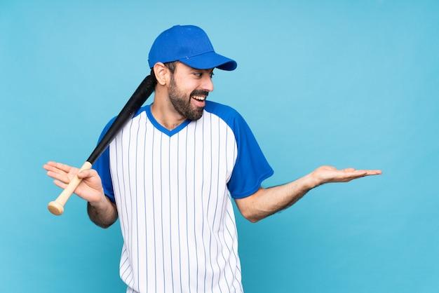 Jovem jogando beisebol sobre isolado azul segurando copyspace com as duas mãos
