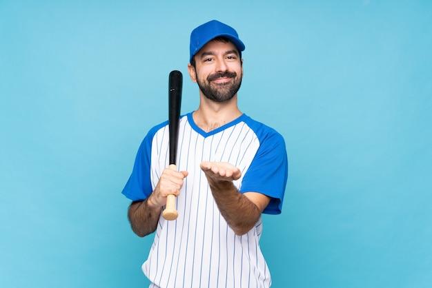 Jovem jogando beisebol sobre isolado segurando copyspace imaginário na palma da mão para inserir um anúncio