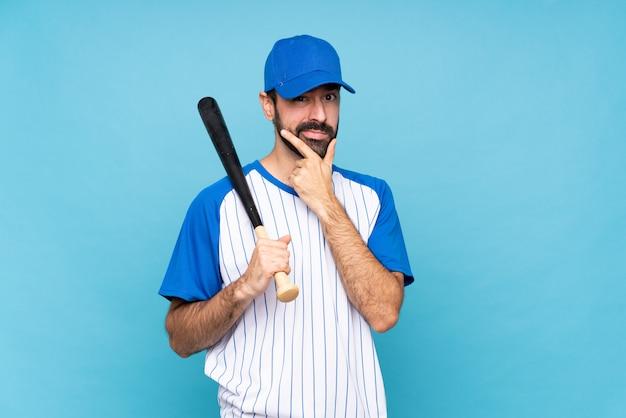Jovem jogando beisebol sobre o pensamento isolado de parede azul