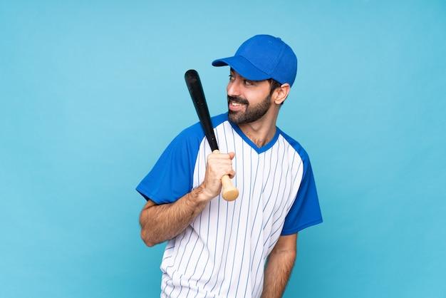 Jovem jogando beisebol sobre parede azul isolada com os braços cruzados e feliz