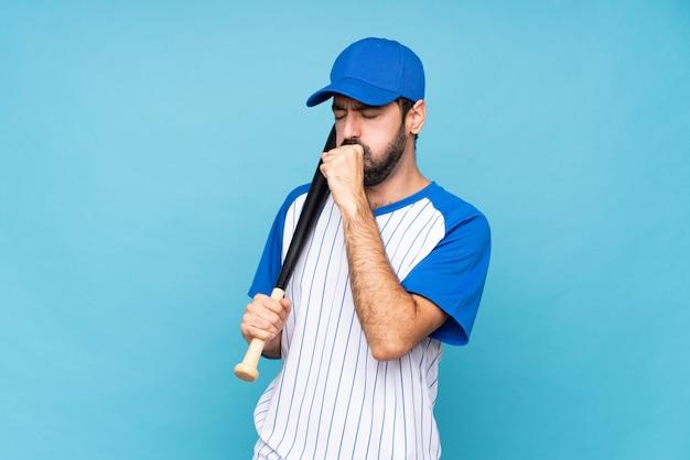 Jovem jogando beisebol sobre parede azul isolada está sofrendo com tosse e se sentindo mal