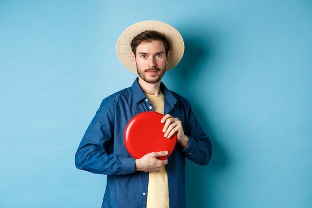 Jovem jogando frisbee, jogando nas férias de verão, de pé no chapéu de palha sobre fundo azul.