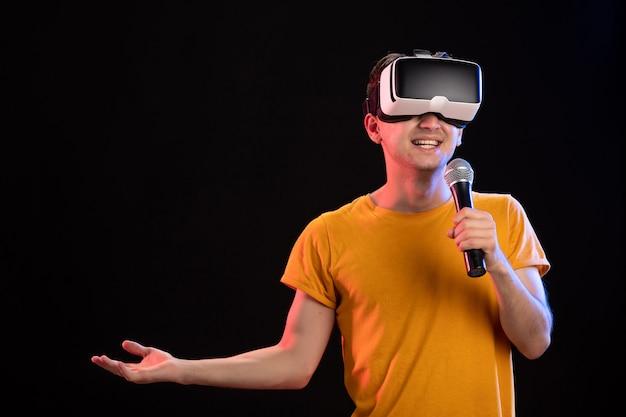 Jovem jogando realidade virtual e cantando em jogos de tecnologia de visão no escuro