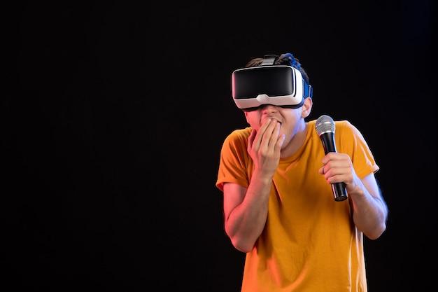 Jovem jogando realidade virtual e cantando na superfície escura