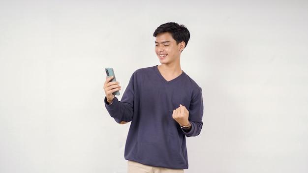 Jovem jogando seu smartphone com entusiasmo isolado no fundo branco