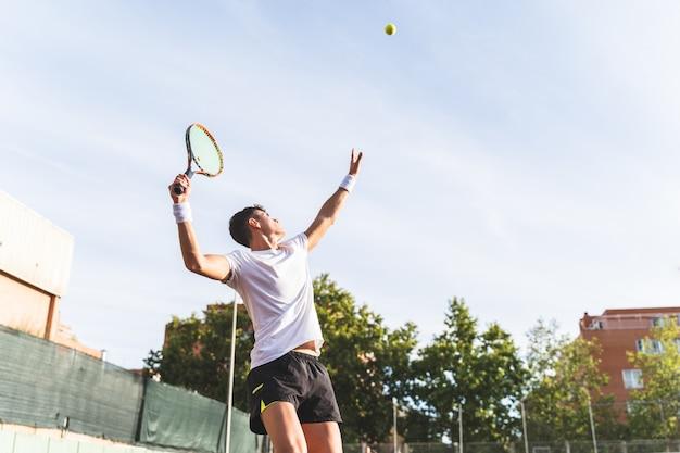 Jovem jogando tênis ao ar livre.