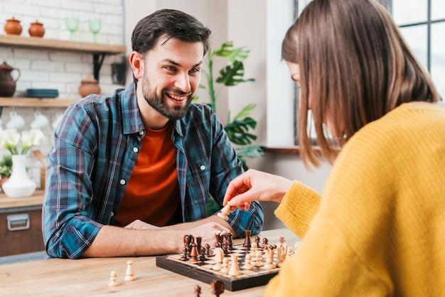 Jovem jogando xadrez com sua esposa em casa