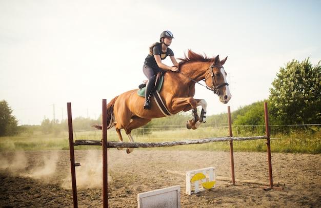 Jovem jóquei em seu cavalo saltando sobre um obstáculo