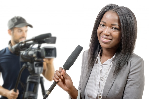 Jovem jornalista afro-americana com um microfone e um operador de câmara