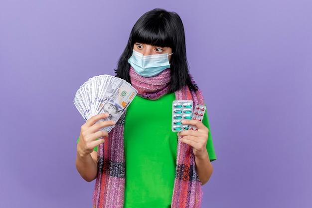 Jovem, jovem, doente, caucasiana, impressionada, usando máscara e lenço segurando dinheiro e pacotes de cápsulas, olhando para o dinheiro isolado no fundo roxo com espaço de cópia