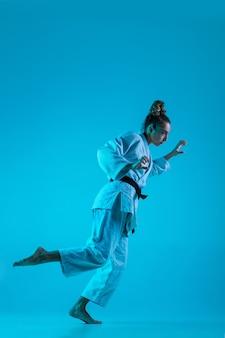 Jovem judoca profissional isolada no fundo azul do estúdio em néon