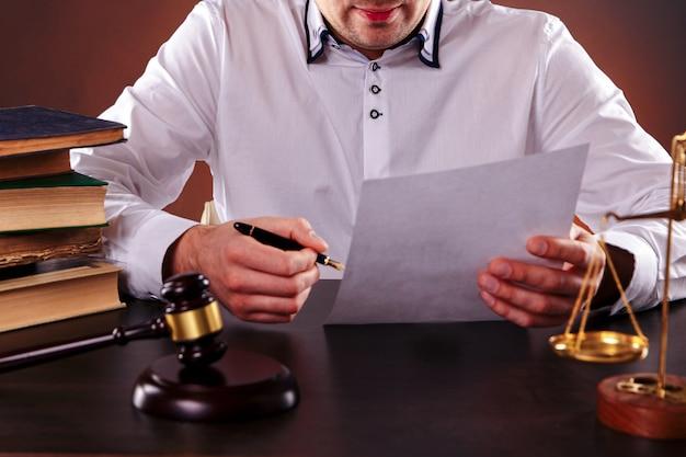 Jovem juiz em sua mesa, trabalhando com documentos em papel.