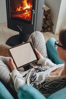 Jovem junto à lareira, sentada em uma poltrona aconchegante, com um cobertor quente, usando um tablet