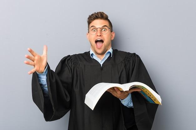 Jovem jurista segurando um livro celebrando uma vitória ou sucesso