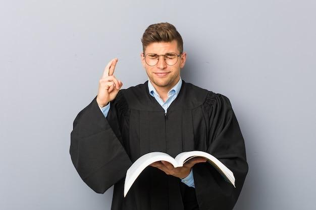 Jovem jurista segurando um livro cruzando os dedos por ter sorte