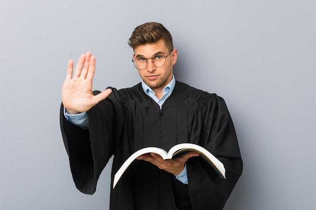 Jovem jurista segurando um livro de pé com a mão estendida, mostrando o sinal de pare, impedindo você.