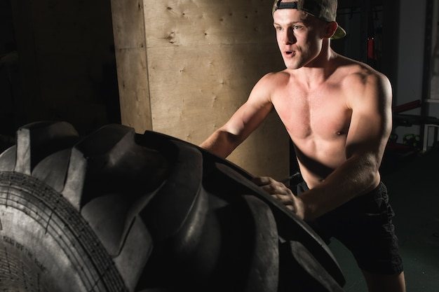 Jovem lançando pneu no ginásio