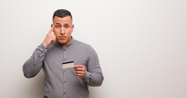 Jovem, latim, homem, segurando, um, cartão crédito, pensando, um, idéia