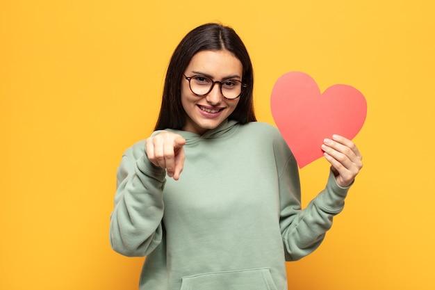 Jovem latina apontando para a câmera com um sorriso satisfeito, confiante e amigável, escolhendo você