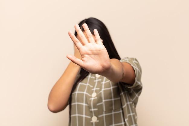 Jovem latina cobrindo o rosto com a mão e colocando a outra mão na frente para parar a câmera, recusando fotos ou imagens