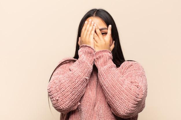 Jovem latina cobrindo o rosto com as mãos, espiando por entre os dedos com expressão de surpresa e olhando para o lado