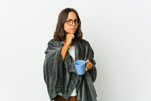 Jovem latina com cobertor suspeito, incerto, examinando você.