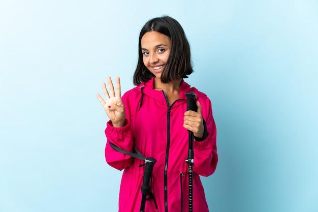 Jovem latina com mochila e bastões de trekking azul feliz e contando quatro com os dedos