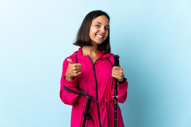Jovem latina com mochila e bastões de trekking isolados no azul com polegares para cima, porque algo de bom aconteceu