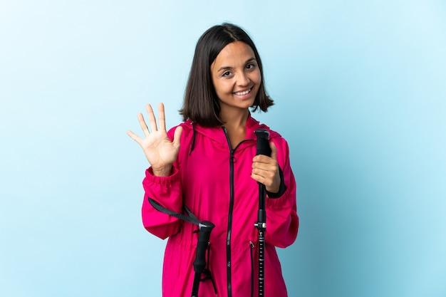 Jovem latina com mochila e bastões de trekking isolados no azul, contando cinco com os dedos