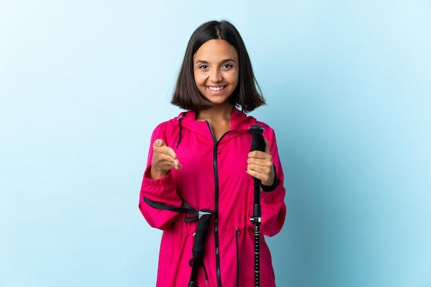 Jovem latina com mochila e pólos de trekking isolados no azul, apertando as mãos para fechar um bom negócio