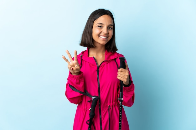 Jovem latina com mochila e pólos de trekking isolados no azul feliz e contando três com os dedos