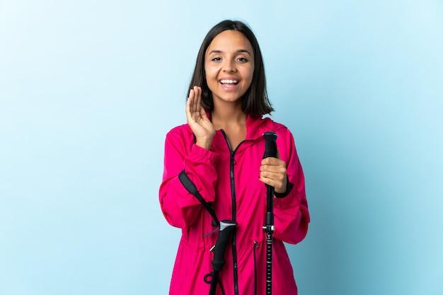 Jovem latina com mochila e pólos de trekking isolados no azul gritando com a boca aberta