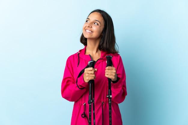 Jovem latina com mochila e pólos de trekking isolados no azul, olhando para o lado e sorrindo
