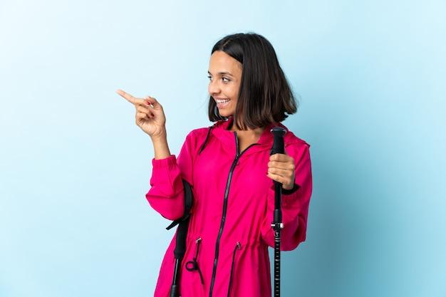 Jovem latina com mochila e pólos de trekking isolados no dedo apontando azul para o lado e apresentando um produto