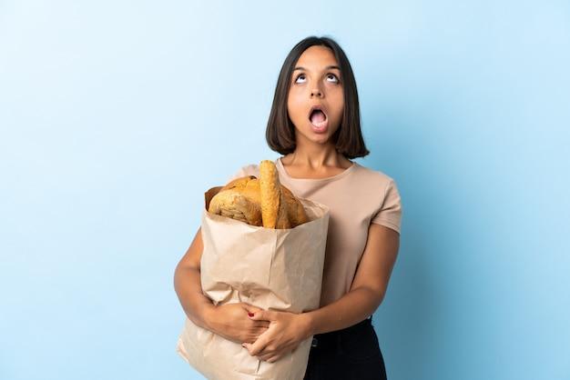 Jovem latina comprando alguns pães isolados no azul, olhando para cima e com expressão de surpresa