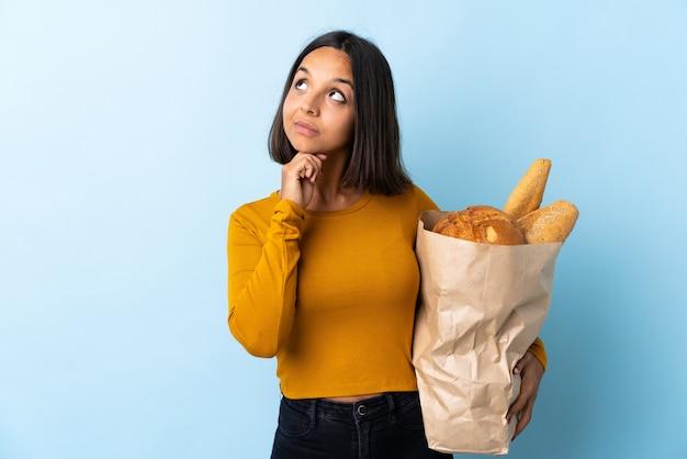 Jovem latina comprando alguns pães isolados no azul, olhando para cima enquanto sorrindo