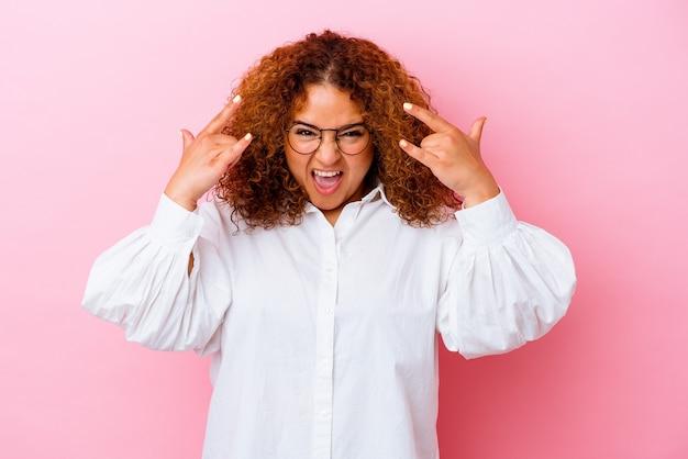 Jovem latina curvilínea isolada na parede rosa, mostrando um gesto de chifres como um conceito de revolução.