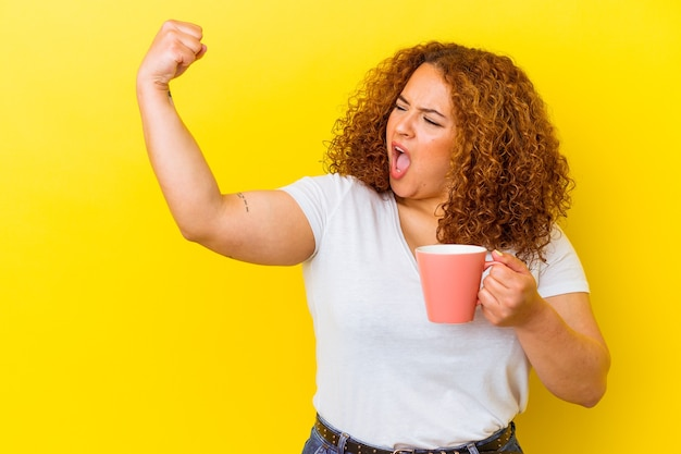 Jovem latina curvilínea mulher segurando uma xícara isolada em fundo amarelo, levantando o punho após uma vitória, o conceito de vencedor.