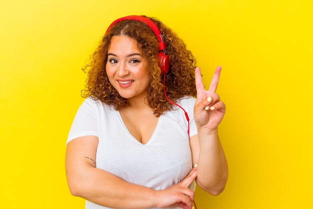 Jovem latina curvilínea ouvindo música isolada em fundo amarelo, mostrando o número dois com os dedos.