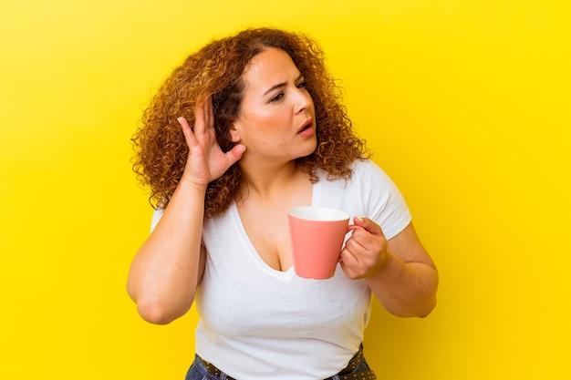 Jovem latina curvilínea segurando um copo isolado no fundo amarelo, tentando ouvir uma fofoca.