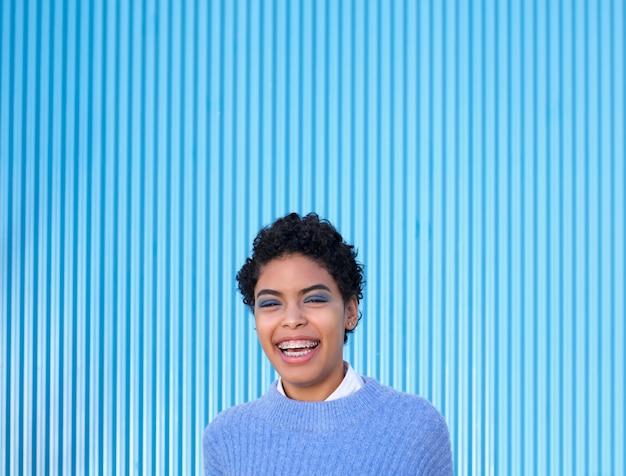 Jovem latina em pé casual na parede azul