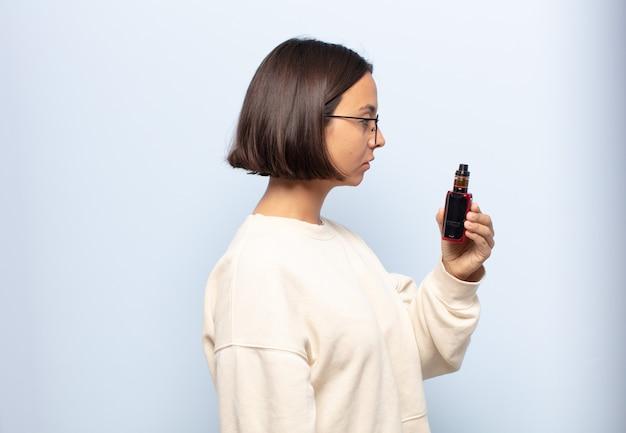 Jovem latina em vista de perfil olhando para copiar o espaço à frente, pensando, imaginando ou sonhando acordada