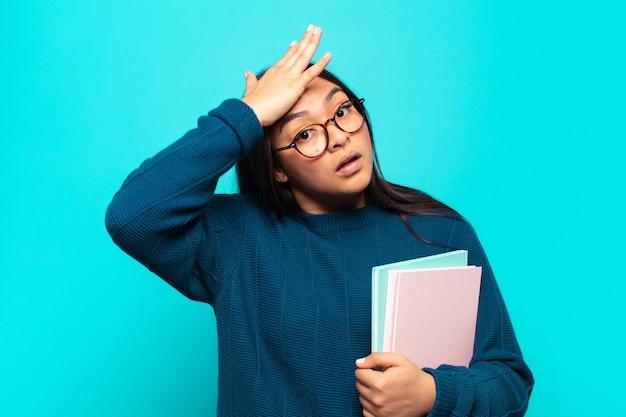 Jovem latina erguendo a palma da mão na testa pensando oops, depois de cometer um erro estúpido ou lembrar, sentindo-se burra