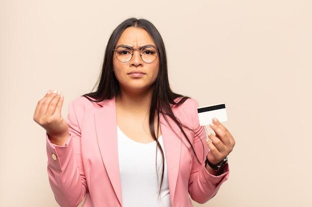 Jovem latina fazendo capice ou gesto de dinheiro, mandando você pagar suas dívidas!