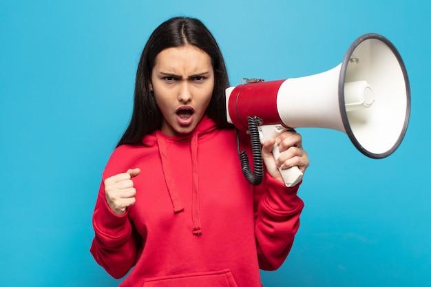 Jovem latina gritando agressivamente com uma expressão de raiva ou com os punhos cerrados celebrando o sucesso