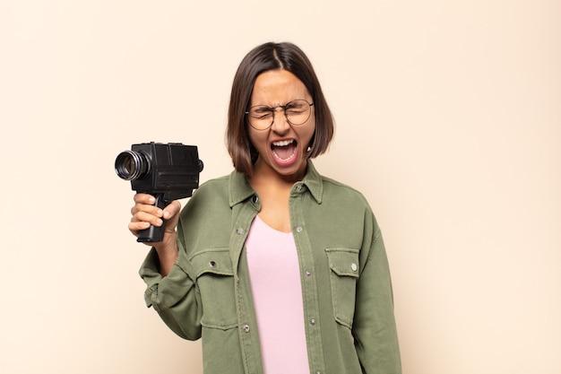 Jovem latina gritando agressivamente, parecendo muito zangada, frustrada, indignada ou irritada, gritando não