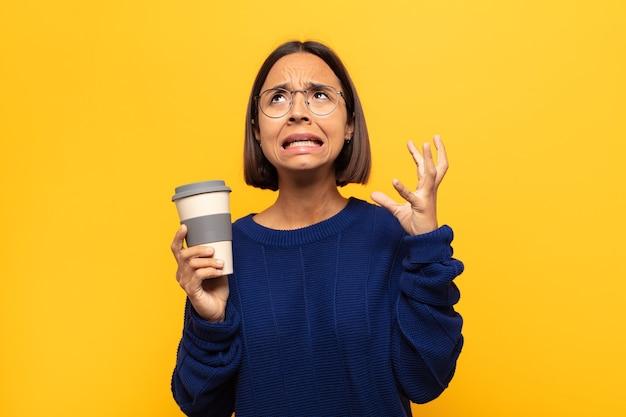 Jovem latina gritando com as mãos ao alto, sentindo-se furiosa, frustrada, estressada e chateada
